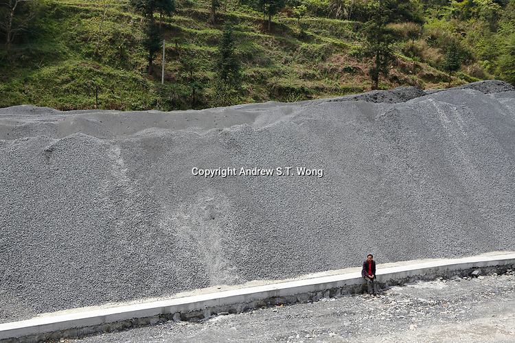 A man sits at a construction site of a highway at Wangmo County in China's southwestern Guizhou Province, April 2019.