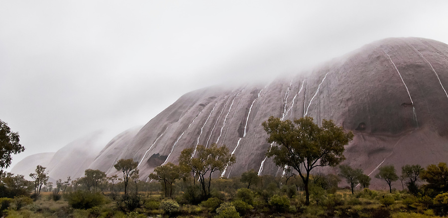 14 Oct 2010Waterfalls cascade down the face of Uluru after torrential overnight rain<br /> Heavy cloud rests on Uluru as streams of water pour down the flanks of the red rock. <br /> Uluru rises from spinifex and Mulga desert plains about 450km south west of Alice Springs