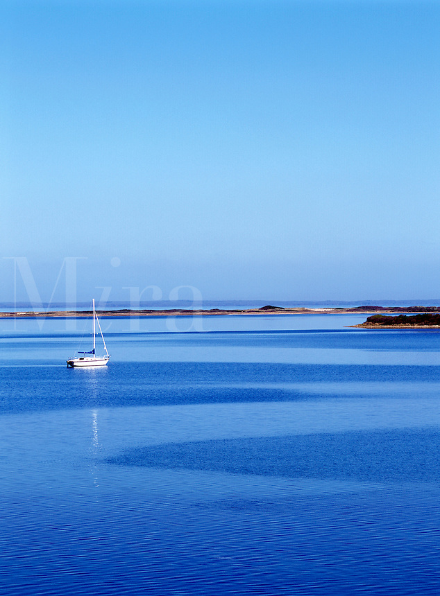 Single white sailboat at mooring on deep blue water. Texture on water. Great Salt Pond, Block Island, Rhode Island.