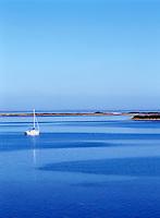 Single white sailboat at mooring on deep blue water. Texture on water. Great Salt Pond, Block Island, Rhode Island.