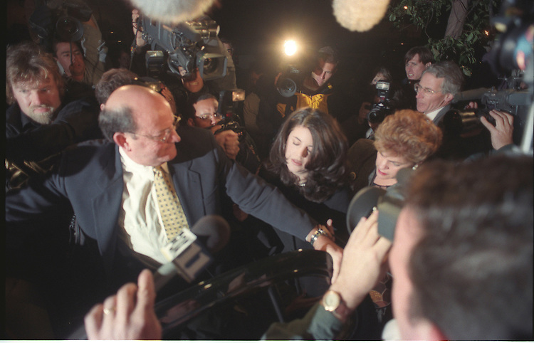 Covering her face, Monica Lewinsky and her stepmother Barbara Lewinsy leave in a car after pushing through a large throng of media after leaving a Santa Monica California restaurant Thursday February 5, 1998.<br /> Photo: Gerard Burkhart)