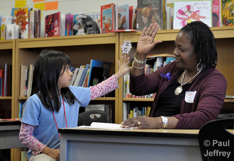 Rose Simmons (right) celebrates with Esther Solis as the girl masters reading a book during a session of the Schools of Hope program at Cesar Chavez Elementary School in Grand Rapids, Michigan. The after school program, which helps children who are behind in reading skills, is sponsored by the United Methodist Community House, where Simmons is the program director. The UMCH has long been supported by United Methodist Women.