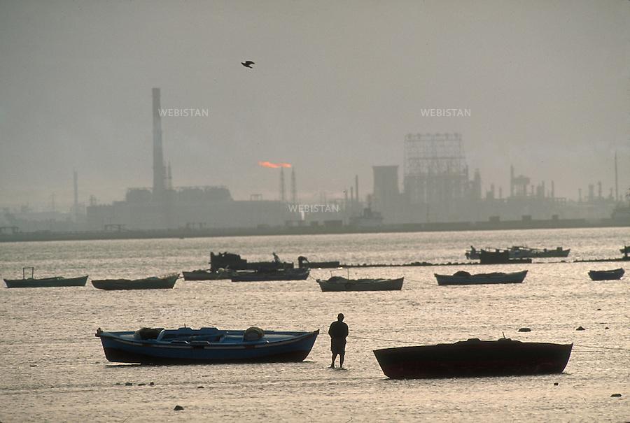 ..Egypt. Suez. 1996. In the harbour bay, Egyptian fishermen wait for the tide to come in to reach their boat. ..Egypte. Suez. 1996. Dans la baie du port, des pecheurs egyptiens attendent la montee de la maree pour rejoindre leurs bateaux.