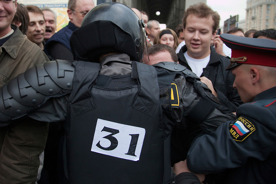Moscow, Russia, 31/08/2010..A riot policeman with an opposition sticker on the back of his flak-jacket as he helps break up an opposition protest in central Moscow and arrest around 70 people. Opposition activists hold regular demonstrations on the 31st day of the month, protesting against restrictions on the freedom of assembly, which is protected by article number 31 of the Russian constitution.
