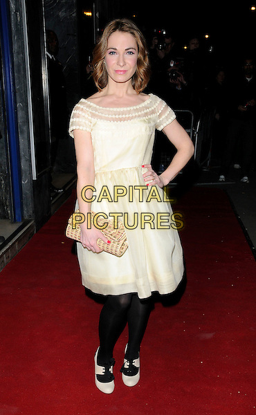 """NIA ROBERTS .""""Patagonia"""" UK film premiere held at the Odeon Covent Garden cinema, Shaftesbury Avenue, London, England, UK, 2nd March 2011..full length gold dress black tights shoes clutch bag pale yellow lace-up cream hand on hip .CAP/CAN.©Can Nguyen/Capital Pictures."""