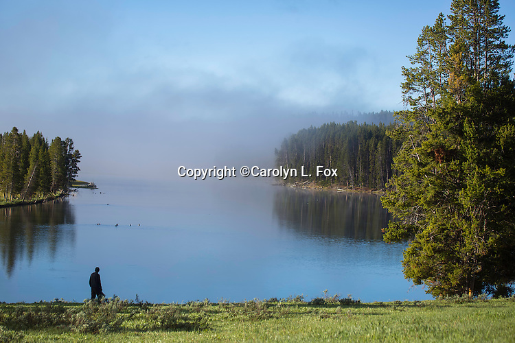 A man stands next to the Yellowstone River, in Yellowstone National Park, on a very foggy morning.