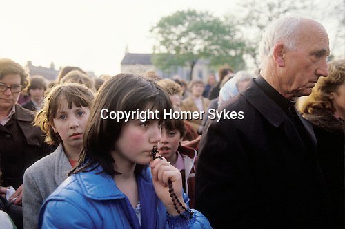 Belfast Ireland 1980s The Troubles. Young Catholic with Rosary at IRA funeral.