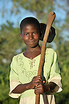 A girl walking home with her hoe in Ekwaiweni, Malawi.