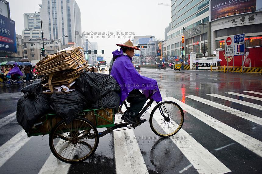 Un raccoglitore di cartone al lavoro per le strade di Hangzhou.<br /> A carton taker at work in the center of Hangzhou