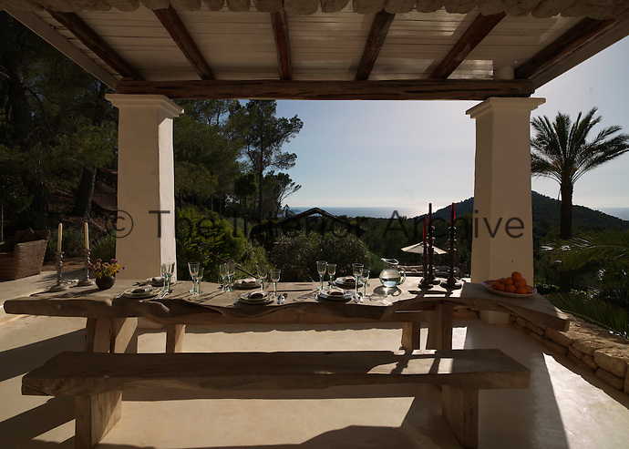 A rustic contemporary table flanked by a pair of wooden benches is laid for dinner on the terrace