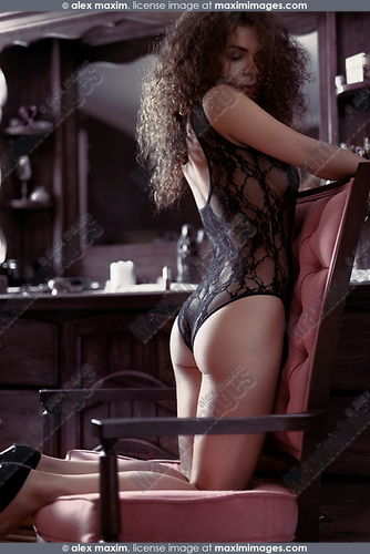 Artistic boudoir portrait of a sexy beautiful woman standing on her knees in a chair by a dresser mirror with thoughtful sensual expression wearing lacy underwear. Vintage retro French style.