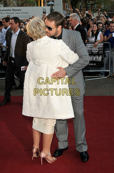 "DAME HELEN MIRREN & RUSSELL CROWE.Attending ""State of Play"" World Film Premiere at Empire cinema, Leicester Square, London, England, UK, .21st April 2009..full length grey gray suit white cream coat back greeting hugging kissing cheek embracing .CAP/PL.©Phil Loftus/Capital Pictures"