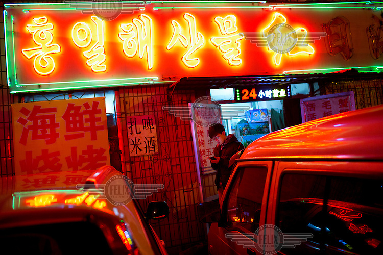 A customer checks his smart phone beneath the neon lights outside the Red Sun restaurant. The establishment specialises in seafood imported from nearby North Korea. /Felix Features