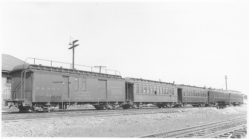 #62 RPO &amp; baggage combined car with roof handrail.  Coaches #284 &amp; #283.  B2 &amp; B3 business cars.  All angled side view.<br /> D&amp;RGW  Antonito, CO  8/30/1941