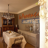 An ornate chandelier hangs above a dining table covered with a white cloth in a country dining room. Glassware is arranged on a grey painted sideboard against one wall.