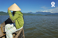 Woman (16) holding conical hat on boat (Licence this image exclusively with Getty: http://www.gettyimages.com/detail/83154206 )