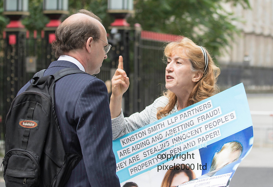pic shows:: Dr Sheida Oraki demonstrates outside  the High Court in London today in her case against Dean and Dean solicitors <br /> <br /> She harangued lawyer Bruce McGregor as he entered the courts<br /> <br /> <br /> <br /> <br /> Pic by Gavin Rodgers/Pixel 8000 Ltd