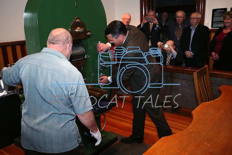 Coiner Ken Hopple, left, watches as Gov. Brian Sandoval mints the first medallion with the second design in a four-part series of Sesquicentennial medallions at the Nevada State Museum, in Carson City, Nev., on Wednesday, Feb. 26, 2014. <br /> Photo by Cathleen Allison/Nevada Photo Source