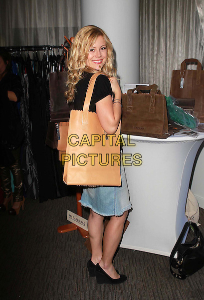 Kim Poirier.Coco Eco Green Emmy Suite Held at At W Hollywood Hotel, Hollywood, California, USA..September 19th, 2012.full length black top jean denim skirt brown bag purse looking over shoulder .CAP/ADM/FS.©Faye Sadou/AdMedia/Capital Pictures.