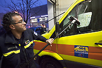 Switzerland. Canton Ticino. Pregassona. Croce Verde Lugano Headquarters. Paramedics team at work cleaning on a Saturday morning the ambulance.  A sticker with the emergency phone number (144) to reach Ticino Soccorso. The man (L) is a professional certified nurse, the woman (C) a volunteer specifically trained in emergency rescue. The Croce Verde Lugano is a private organization which ensure health safety by addressing different emergencies services and rescue services. Volunteering is generally considered an altruistic activity where an individual provides services for no financial or social gain to benefit another person, group or organization. Volunteering is also renowned for skill development and is often intended to promote goodness or to improve human quality of life. Pregassona is a quarter of the city of Lugano. 27.01.2018 © 2018 Didier Ruef
