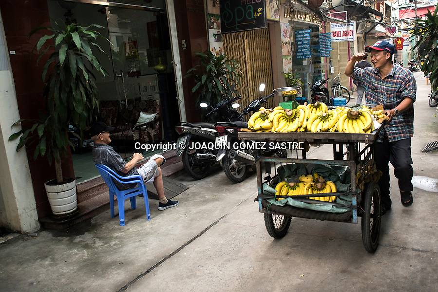 A banana hawker walking down a street in Ho Chi Minh City, capital of Vietnam
