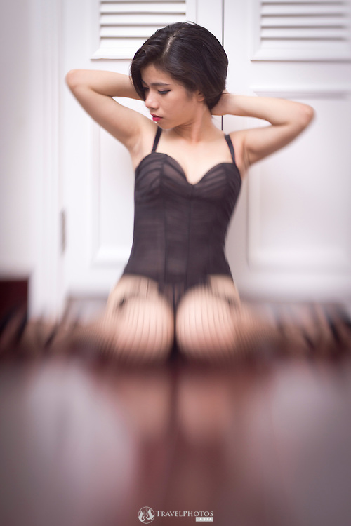 Vietnamese girl posing in a corset and lingerie.