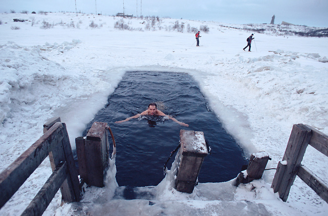 A bather from the Walrus Club swimming in a hole in the ice covering Lake Semyonovskaya. Murmansk, NW Russia.