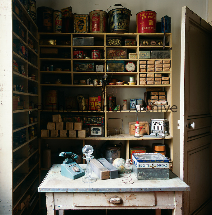 A rustic kitchen corner. Food products and vintage storage tins are displayed on shelving. An old telephone and other items are placed on a table.