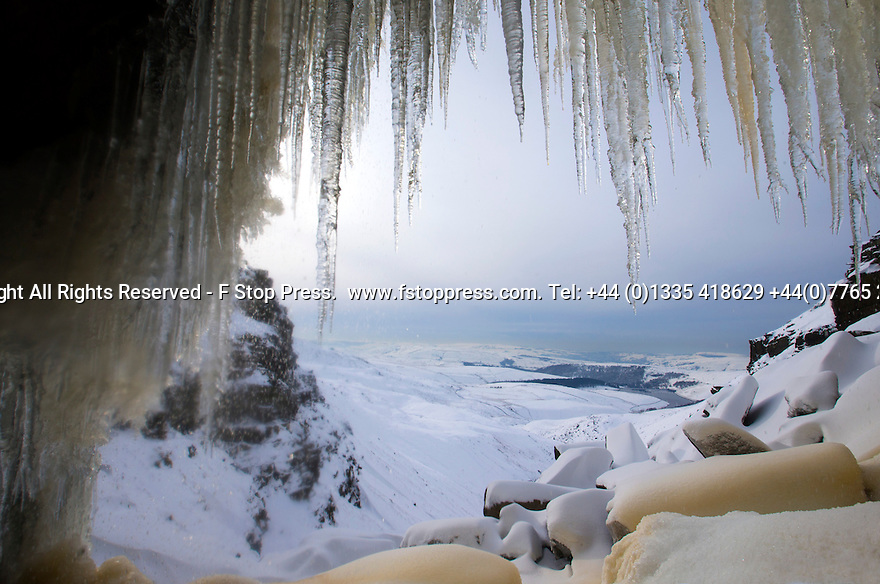 02/02/15<br /> <br /> The view looking from under a 30 metre waterfall that has frozen solid.  At 2,087 ft the cascade known as Kinder Downfall is the only mountain in the Derbyshire Peak District and famously blows up hill in strong winds. <br /> <br /> All Rights Reserved - F Stop Press.  www.fstoppress.com. Tel: +44 (0)1335 418629 +44(0)7765 242650