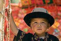 A young Kirgiz boy in the Xinjiang Uygur Autonomous Region of China. Throughout the year, all men, old or young, wear round caps in green, purple, blue or black and covered by a high, square-topped animal skin or felt hat with a rolled-up brim. The inside of the animal skin hat is bordered with black velvet.