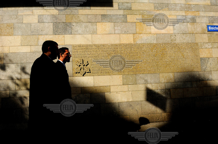Businessmen walk past the exterior wall of the headquarters of Switzerland's largest bank, UBS, as the approach Paradeplatz, the symbolic centre of the Swiss banking industry. The Swiss banking industry holds an estimated 4,000 billion Swiss Francs (USD 4,240 billion) in assets, more than half of it foreign, including CHF 880 billion in undeclared European assets alone, benefiting from the country's famous banking secrecy laws.