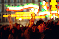 Demonstration in the Zocalo in support of EZLN (Ejercito Zapatista de Liberacion Nacional), the Zapatista agrarian reform movement. Woman supporter of the zapatistas showing V salute. Decorative lights for independence day celebration in background. Mexic