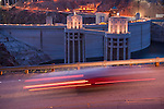 Traffic slows to a crawl on highway US 93 on the crest of Hoover Dam at sundown from the Arizona side showing the intake towers and Nevada side parking garage