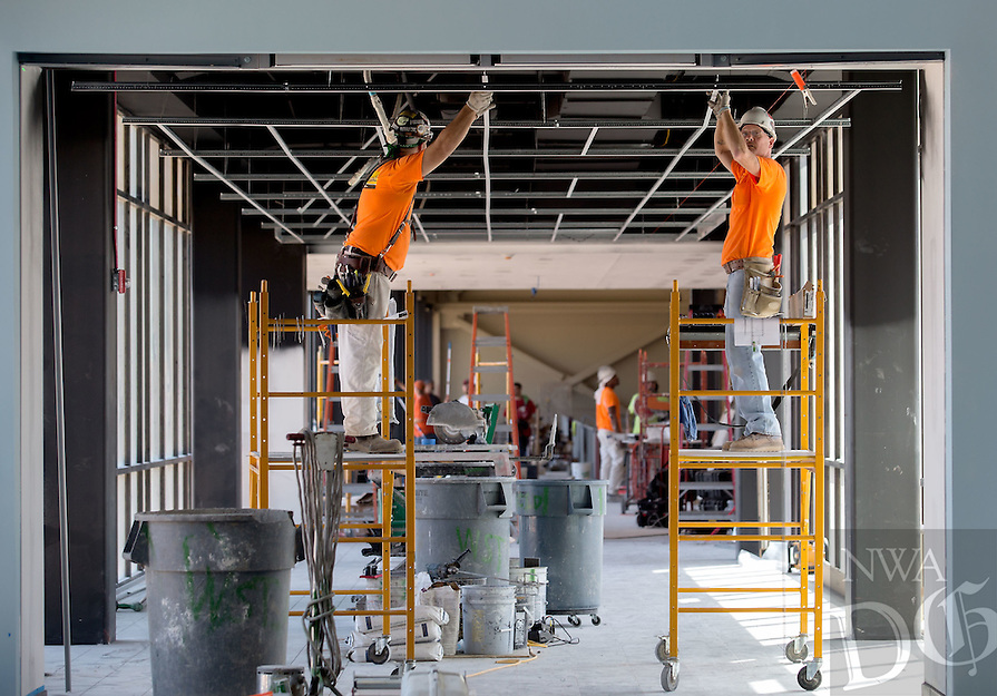 NWA Media/JASON IVESTER --08/21/2014--<br /> Workers continue construction on the walkway to the gymnasium on Thursday, Aug. 21, 2014, inside the new Joplin High School in Joplin, Mo. The school was originally scheduled to open with the rest of the school district on Monday, Aug. 25, but was pushed back to Tuesday, Sept. 2.