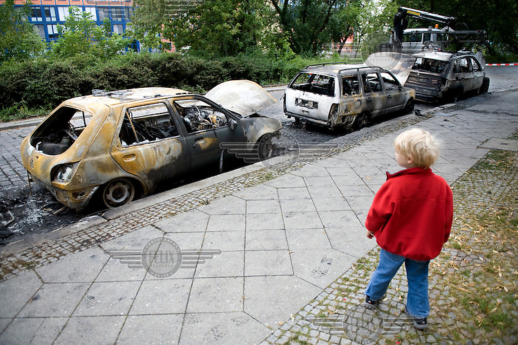 A child walks past burnt out cars in Berlin. The cause of the fire was not immediately known, but investigating police officers said an arson attack is likely.