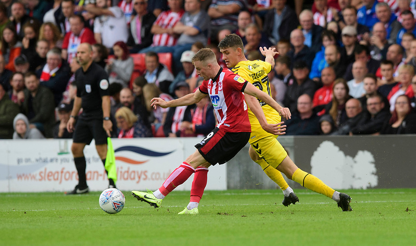 Lincoln City's Joe Morrell vies for possession with Fleetwood Town's Harrison Biggins<br /> <br /> Photographer Chris Vaughan/CameraSport<br /> <br /> The EFL Sky Bet League One - Lincoln City v Fleetwood Town - Saturday 31st August 2019 - Sincil Bank - Lincoln<br /> <br /> World Copyright © 2019 CameraSport. All rights reserved. 43 Linden Ave. Countesthorpe. Leicester. England. LE8 5PG - Tel: +44 (0) 116 277 4147 - admin@camerasport.com - www.camerasport.com