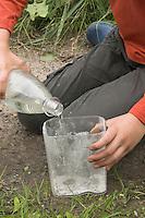 Kinder gießen Tierspur aus Gips, Mädchen füllt Wasser in einen Messbecher