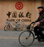 A cyclist passes the Bank of China in Zhengzhou, China..