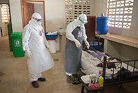 "Tenneh Kennedy, R.N. (right) and Ben Smith, hygienist supervisor, talk with an unconfirmed Ebola patient in the ""red zone"" of the ELWA II ETU in Paynesville, Monrovia, Liberia on Monday, March 9, 2015. The patient, a young girl, ended up testing negative for Ebola and was discharged.<br /> Both health care workers wear a sticker with their portrait on their PPE, part of Occidental College professor Mary Beth Heffernan's PPE Portrait project she has been working on in Liberia. PPE (personal protective equipment) is mandatory for all staff while working in the area with patients, called the ""red zone."" The area is isolated and staff only enter to care for patients at designated times throughout the day, which means human contact for patients is minimal.<br /> (Photo by Marc Campos, Occidental College Photographer) Mary Beth Heffernan, professor of art and art history at Occidental College, works in Monrovia the capital of Liberia, Africa in 2015. Professor Heffernan was there to work on her PPE (personal protective equipment) Portrait Project, which helps health care workers and patients fighting the Ebola virus disease in West Africa.<br />