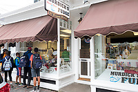 People watch as Daniel Ferguson, 50, (in window at left) shapes fudge at Murdick's Fudge in Edgartown, Martha's Vineyard, Massachusetts, USA. Ferguson is from Jamaica and has an H2B seasonal foreign worker visa. He says 2017 is his sixth summer season working in the fudge shop. During off-months, he returns to Jamaica where he can be with family and escape the cold weather. Most of the shop's workers are seasonal foreign workers. Other companies on Martha's Vineyard and around the US had difficulty obtaining H2B visas, but Murdick's Fudge received all it requested.