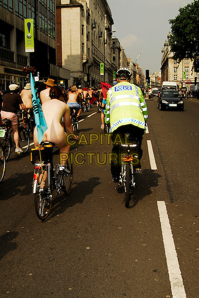 CYCLISTS & POLICE ESCORT.Taking part in The World Naked Bike Ride, which protests on the subject of the world's oil dependency and aims to curb  car culture, London, england, June 9th 2006..full length nude bikes cycling riding bicycle protesters race back behind.CAP/IA.©Ian Allis/Capital Pictures