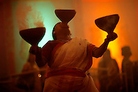 Dhunuchi folk dance performed at Durga Puja festival in Bengal, India. Burning embers of coal are placed in a pot and devotees of the goddess carry 1 - 3 pots as they dance to the unique beat of drummers