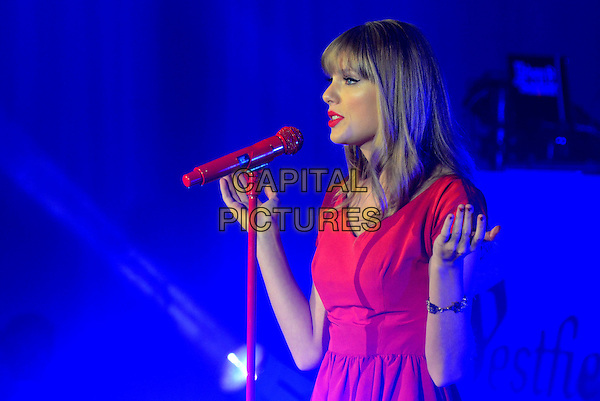 Taylor Swift.at Westfield London shopping centre to switch on Christmas Lights. England..6th November 2012.on stage in concert live gig performance performing music half length red dress singing profile hand arm.CAP/WIZ.© Wizard/Capital Pictures.