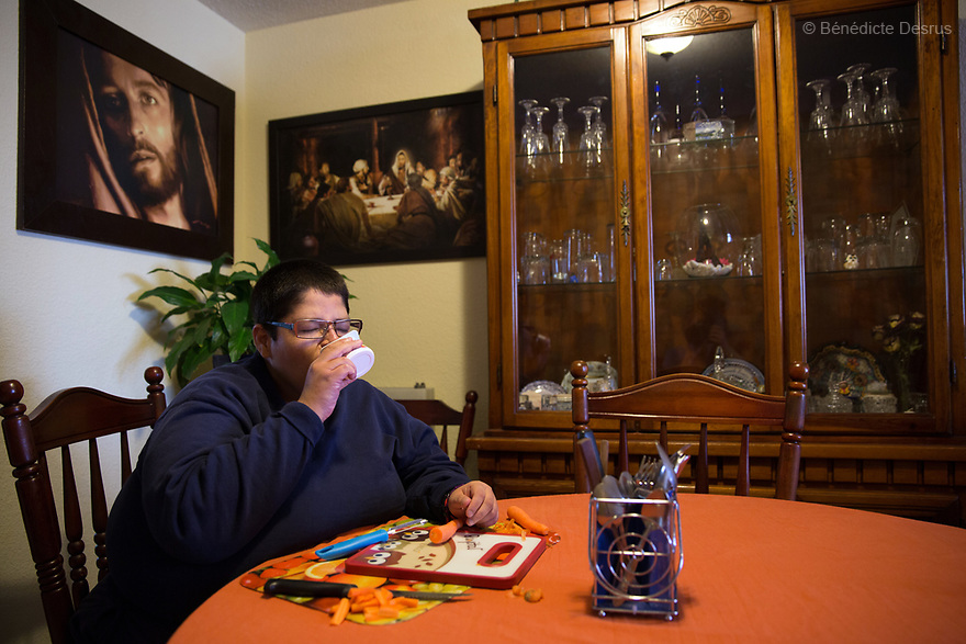 """Jorge eats yogurt as he peels carrots for lunch at his home in Puebla, Mexico on April 23, 2017. Jorge Antonio Moreno Gaytán, a 34-year-old Mexican man, lives with his parents in Puebla, Mexico. He was diagnosed with Prader-Willi syndrome at age seven. He weighs 136 kilos (300 pounds) and stands 152 centimeters (4 feet 12 inches). Jorge is in the process of getting bariatric surgery. As a teenager, he would pawn his siblings' belongings in order to have money to buy food. He was also known to leave restaurants without paying. """"Our worst enemy is hunger, it's what will kill us"""", Jorge says. He is now part of a sports team for people with disabilities. He has been in a relationship for 11 years with, Maria Guadalupe Pilar Saucedo Granda, known as """"Lupita', also diagnosed with Prader-Willi syndrome. Prader-Willi Syndrome (PWS) is a rare genetic disorder caused by an abnormality in chromosome 15. Innewbornssymptoms includeweak muscle tone (hypotonia), poor appetite and slow development. In childhood the person experiences a sensation of constant hunger no matter how much he/she eats which often leads toobesityandType 2 diabetes. There may also be mild to moderateintellectual impairmentand behavioral problems. Physical characteristics include a narrow forehead, small hands and feet, short in stature, and light skin color. Prader-Willi syndrome has no known cure. However, with early diagnosis and treatment such as growth hormone therapy, the condition may improve. Strict food supervision is typically required. PWSaffects an estimated 1 in 10,000 to 30,000 people worldwide. (Photo by Bénédicte Desrus)"""