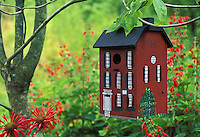 birdhouse as Faux brick townhouse settled in the red garden of monard, and red flowers with dogwood tree. Midwest USA