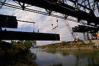 Tethered to a safety line, a worker walks on a huge steel beam that will span a river. Steel worker.