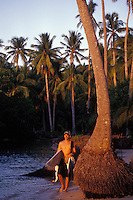 Surfer walking home at sunset from a day boat trip in the Philippines