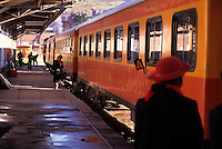 The bright orange and yellow train from Puno to Cusco, Peru at the station in Puno