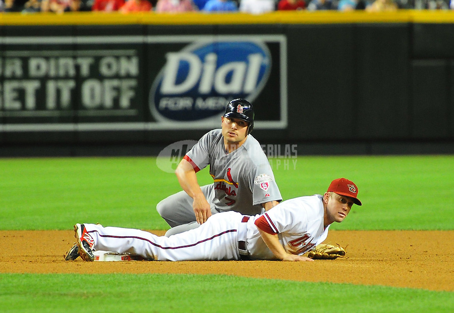 May 8, 2012; Phoenix, AZ, USA; Arizona Diamondbacks infielder Aaron Hill lays on the ground in front of St. Louis Cardinals base runner Matt Holliday after turning a double play in the eighth inning at Chase Field. Mandatory Credit: Mark J. Rebilas-
