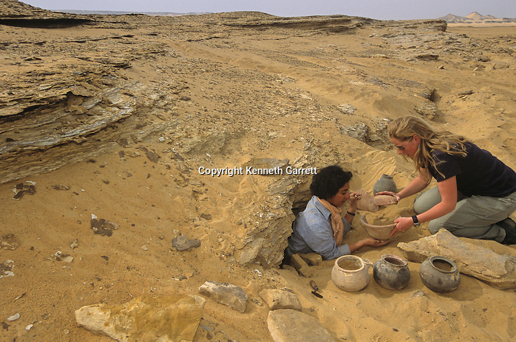 Salima Ikram and Alison Gascoigne remove vessels from escarpment near Ain Dabashiya, Darb el-Arbaein, trade route, Egypt; Ancient Cultures; Archaeologist; Salima Ikram; Kharga Oasis; Desert; oasis